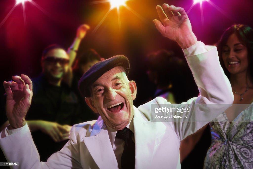 Hispanic senior man dancing in nightclub : Stock Photo