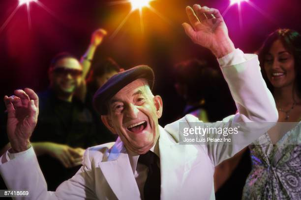 Hispanic senior man dancing in nightclub
