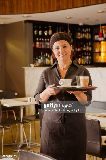 Hispanic server with tray of coffee in cafe