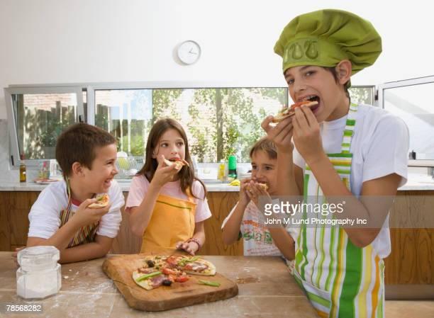 Hispanic siblings eating pizza