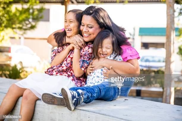 hispanic siblings laughing in the park - mexican ethnicity stock pictures, royalty-free photos & images