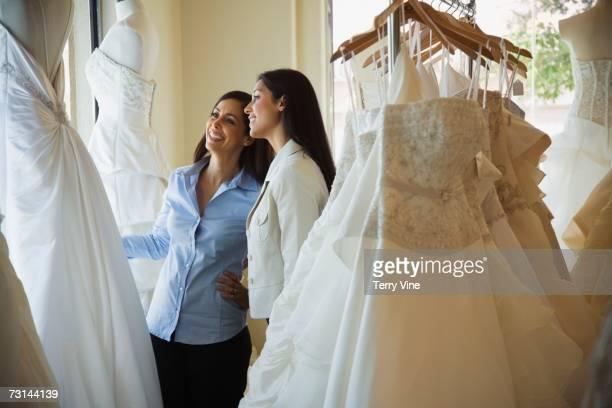 Hispanic sisters looking at wedding dresses in shop