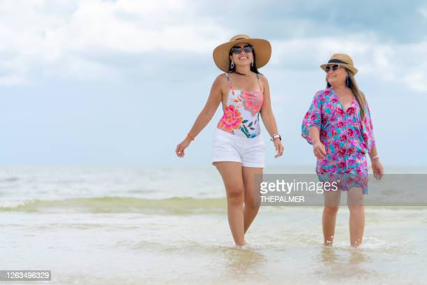 hispanic sisters walking on a florida beach - fort myers stock pictures, royalty-free photos & images
