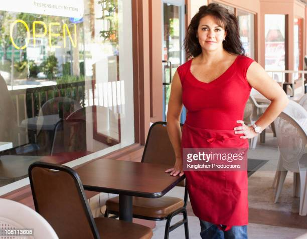 Hispanic small business owner standing on patio