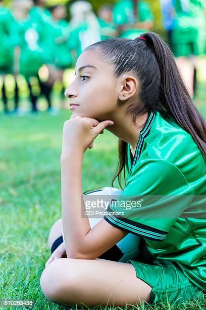 Hispanic soccer athlete waits for game to start