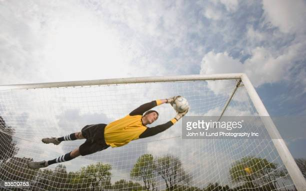 hispanic soccer goalie catching soccer ball in air - goalie goalkeeper football soccer keeper stock pictures, royalty-free photos & images