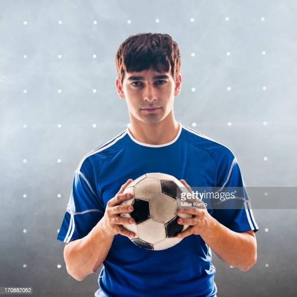 Hispanic soccer player holding ball
