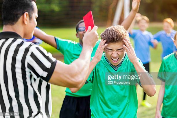 Hispanic soccer player yells while being shown red card