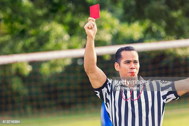 Hispanic soccer referee holds red card while blowing whistle
