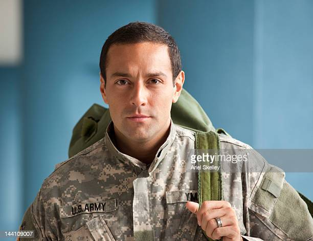 hispanic soldier in uniform holding backpack - army soldier stock photos and pictures