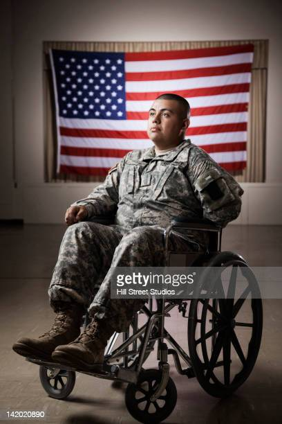 hispanic soldier in wheelchair near american flag - injured soldier stock photos and pictures