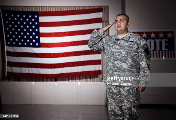 hispanic soldier saluting american flag - marine corps flag stock pictures, royalty-free photos & images