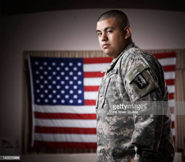 hispanic soldier standing in front of american flag - marines military stock photos and pictures