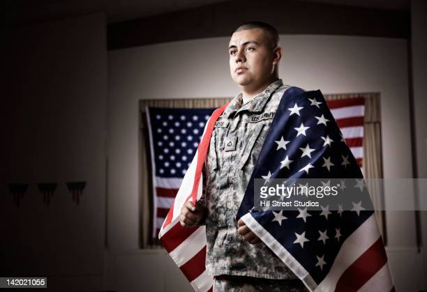 hispanic soldier wrapped in american flag - marine corps flag stock pictures, royalty-free photos & images