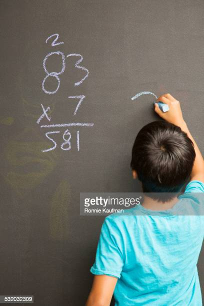 Hispanic student doing math problem on chalkboard in class
