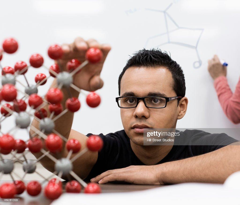 Hispanic student examining molecular model : Stock Photo