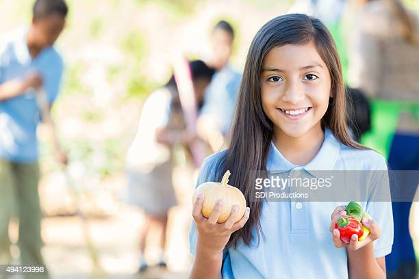 Hispanic student holding vegetables from garden during farm field trip