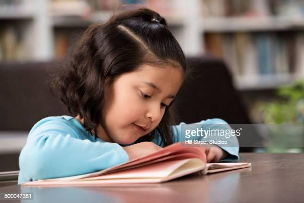 hispanic student reading in library - 綴り ストックフォトと画像
