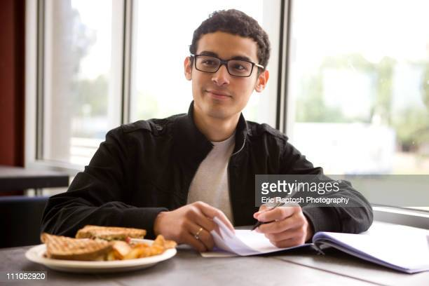 Hispanic student studying in diner and having lunch