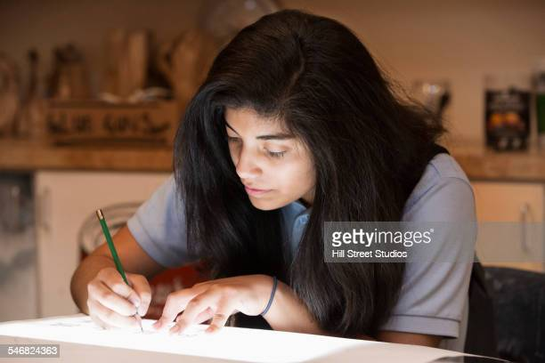 Hispanic student tracing on light box