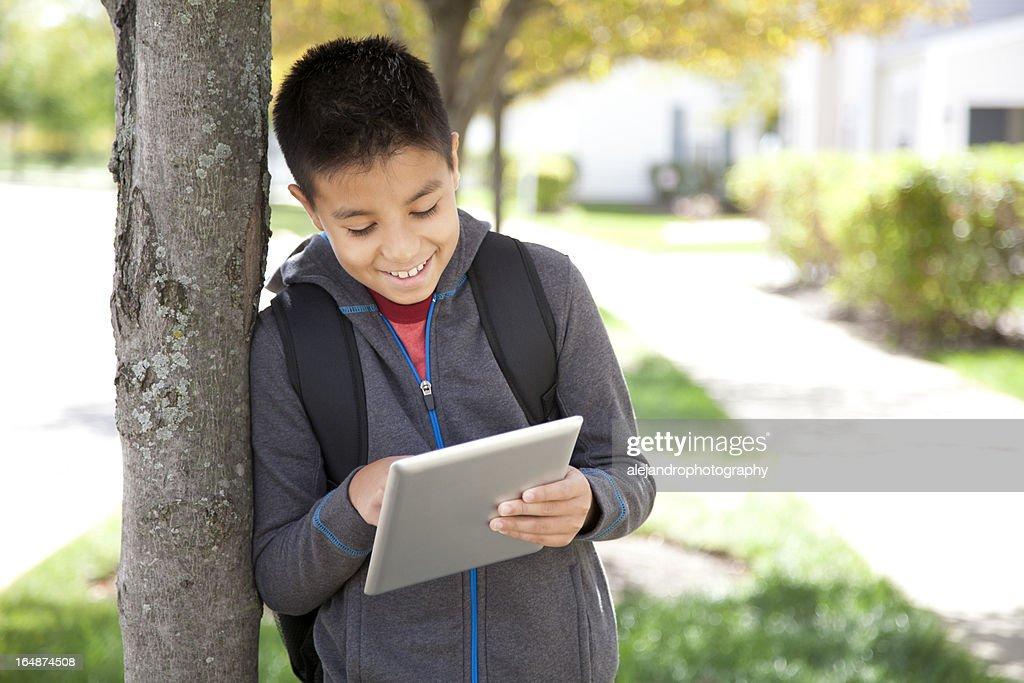 Hispanic student using a digital tablet : Stock Photo