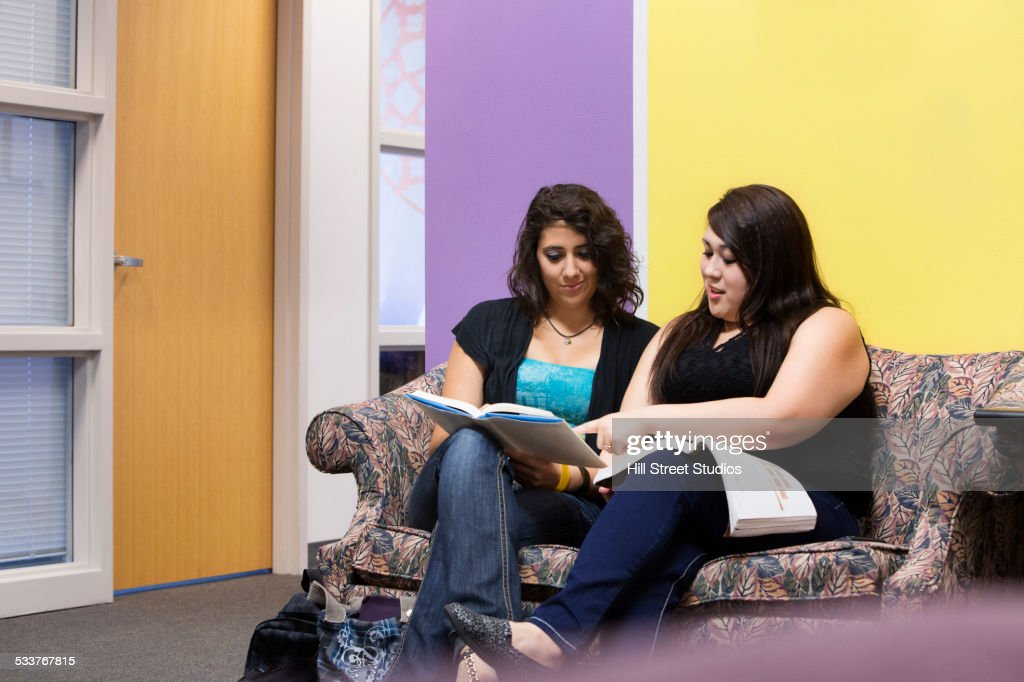 Hispanic students reading together in campus lounge : Foto stock