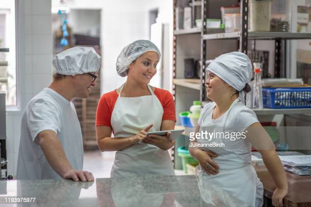 hispanic supervisor using tablet and talking with coworkers - persons with disabilities stock pictures, royalty-free photos & images