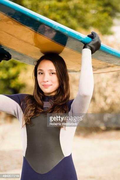 Hispanic surfer carrying board on beach