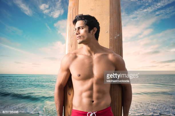hispanic surfer with a dramatic sunset at the ocean - shirtless stock pictures, royalty-free photos & images