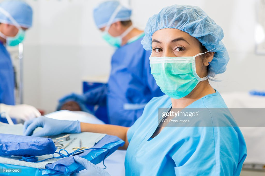 Hispanic surgical nurse or technician assisting with surgery in hospital : Stock Photo