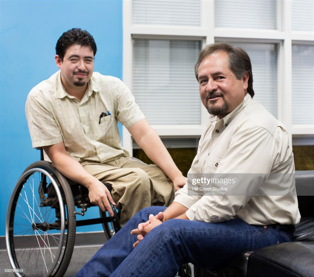 Hispanic teacher and student smiling in campus lounge : Foto stock