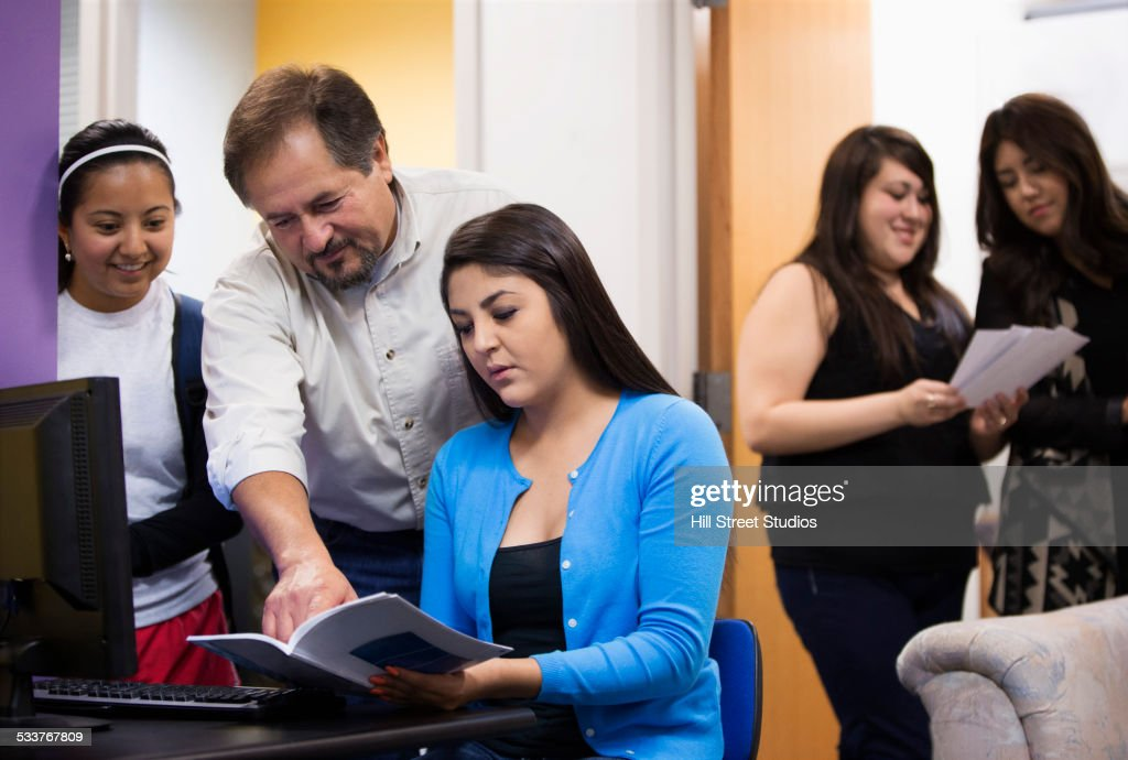 Hispanic teacher and students working together : Foto stock