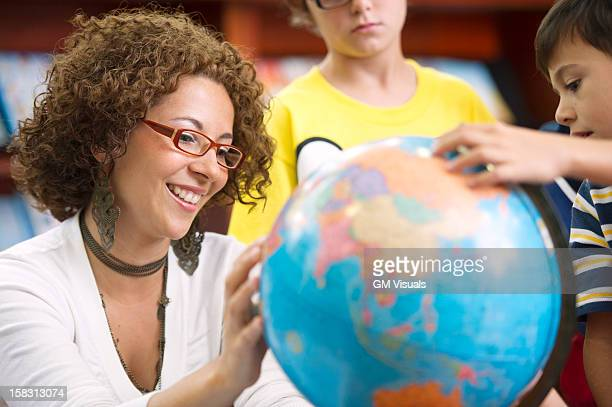 Hispanic teacher helping students with globe