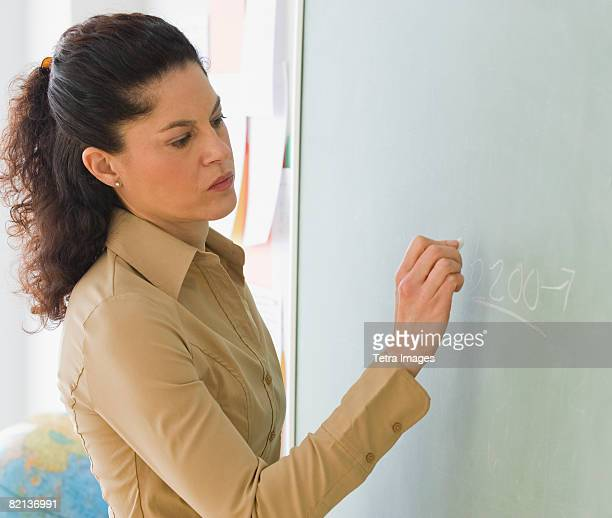 Hispanic teacher writing on blackboard