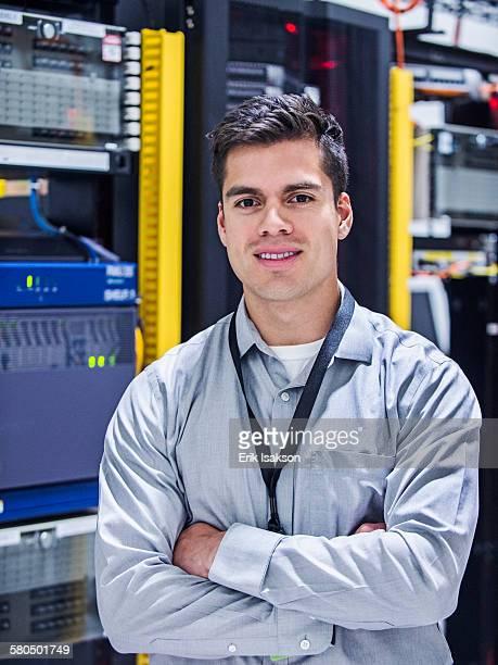Hispanic technician smiling in server room