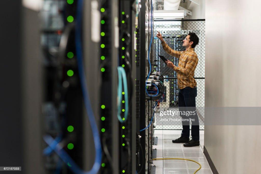 Hispanic technician working in computer server room : Stock Photo