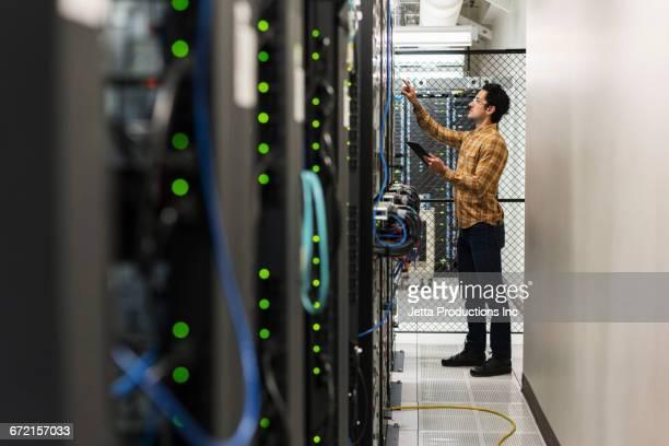 hispanic technician working in computer server room - servidor de rede - fotografias e filmes do acervo