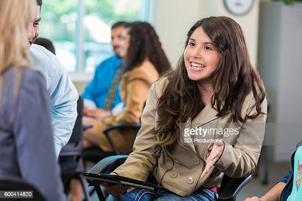 Hispanic teen girl talking during support group therapy session