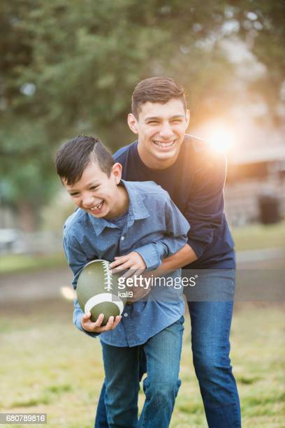 hispanic teenage boy, brother playing football in park - brother stock photos and pictures