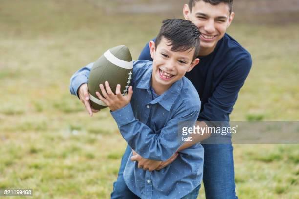 Hispanic teenage boy, brother playing football in park