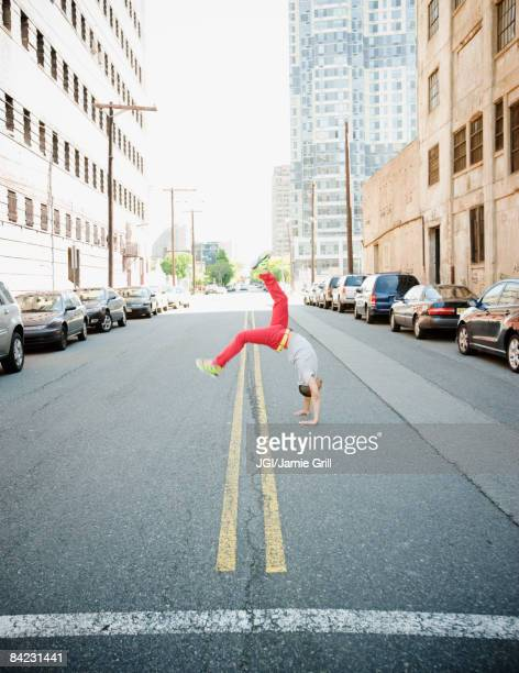 Hispanic teenage boy doing back flip in urban street