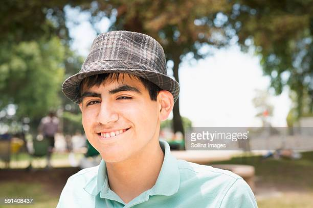 hispanic teenage boy smiling in park - fedora stock pictures, royalty-free photos & images