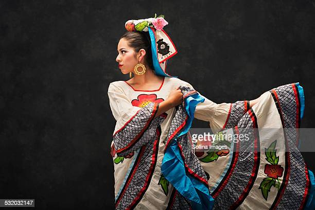 Hispanic teenage girl dancing in Sinaloa Folkloric dress