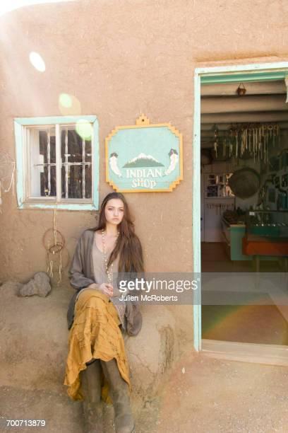 Hispanic teenage girl sitting near doorway to shop