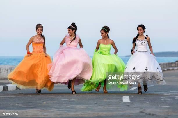 Hispanic teenage girls running in ball gowns