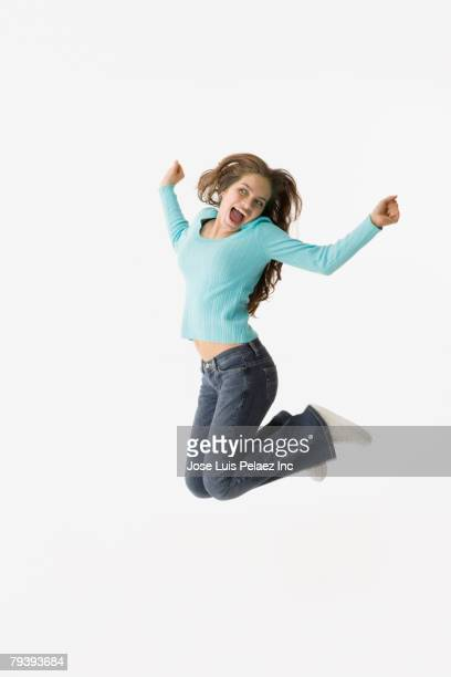 Hispanic teenaged girl jumping in air