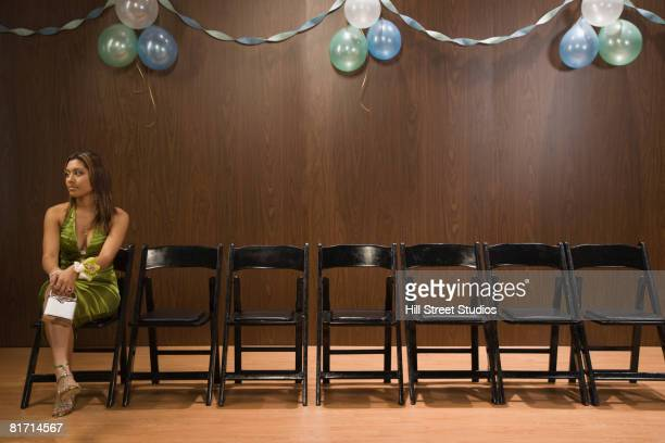 Hispanic teenaged girl sitting alone at prom