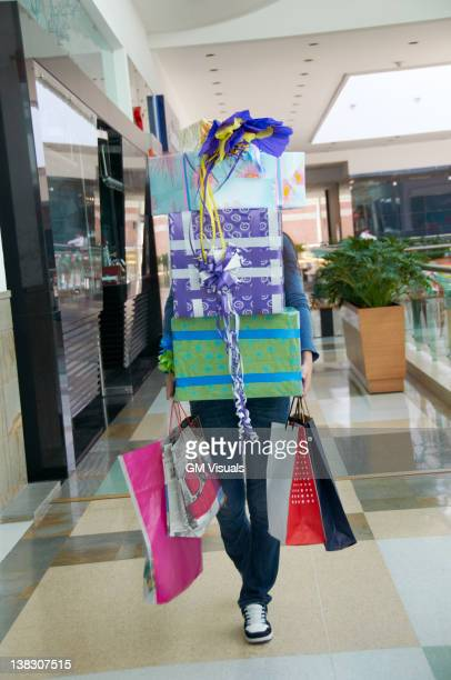 Hispanic teenager carrying gifts in shopping mall