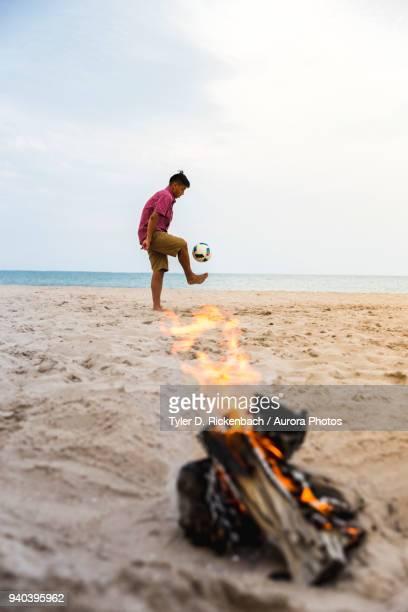 hispanic teenager playing soccer on beach, sheboygan, wisconsin, usa - ウィスコンシン州シボイガン ストックフォトと画像