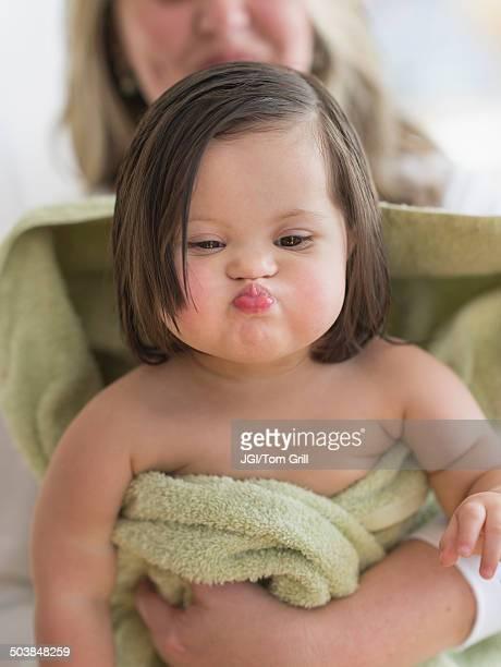 Hispanic toddler making faces after bath